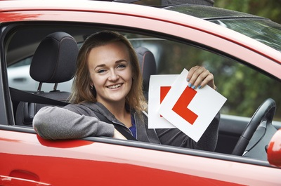 Girl sitting in a car smiling as she has just passed her driving test